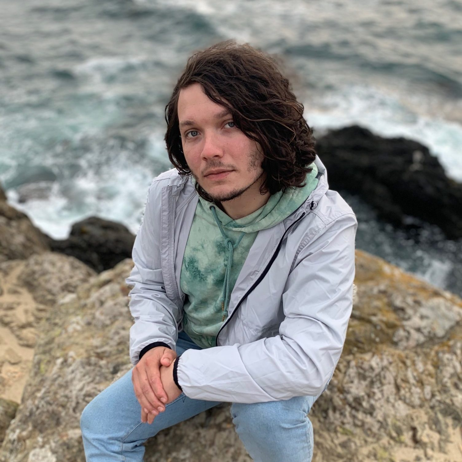 Jordan James Harvill is on a shore near the ocean. He is in his 30s, and has shoulder-length brown wavy hair and is wearing a green hood, a gray sweater, and blue jeans.